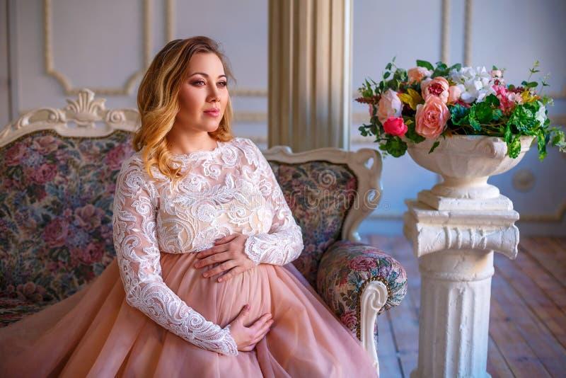 一名孕妇在一件美丽的礼服坐长沙发 母性的概念 库存照片
