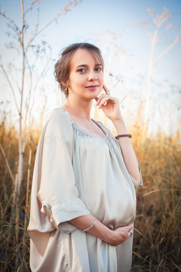 一名孕妇的画象日落光的 免版税库存图片