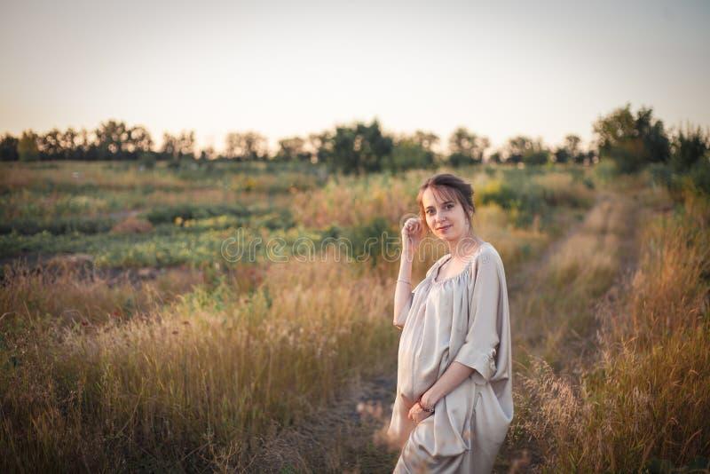 一名孕妇的画象日落光的 免版税库存照片