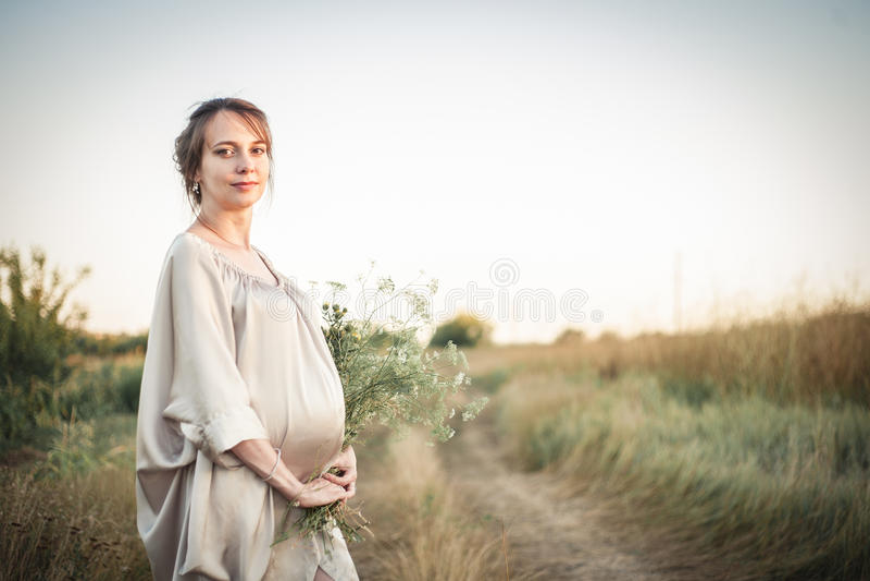 一名孕妇的画象日落光的 库存图片