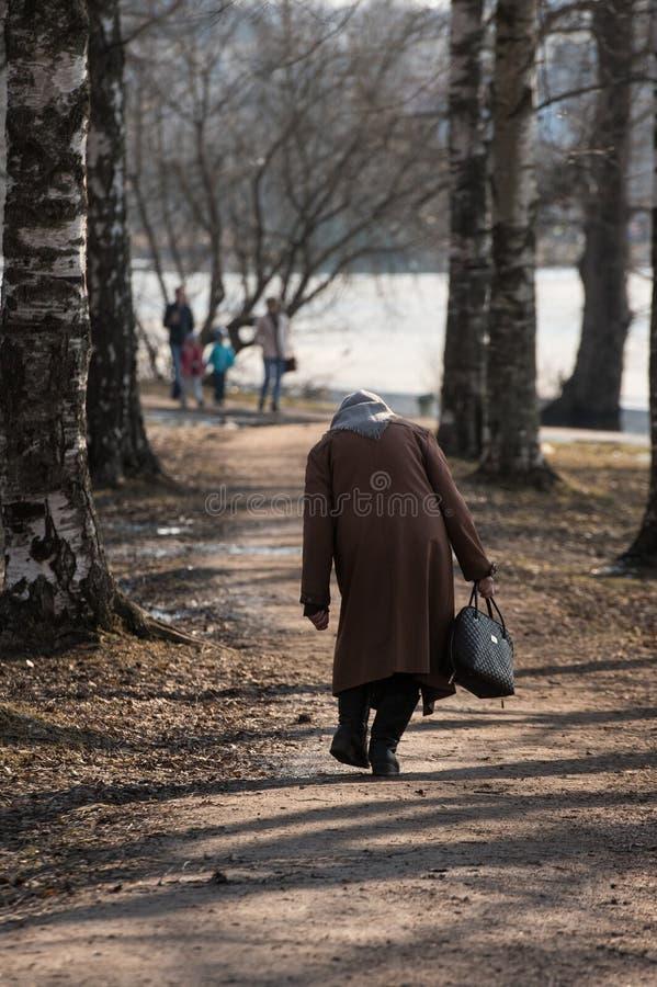 一名孤独的病的弯的妇女沿公园胡同走 图库摄影