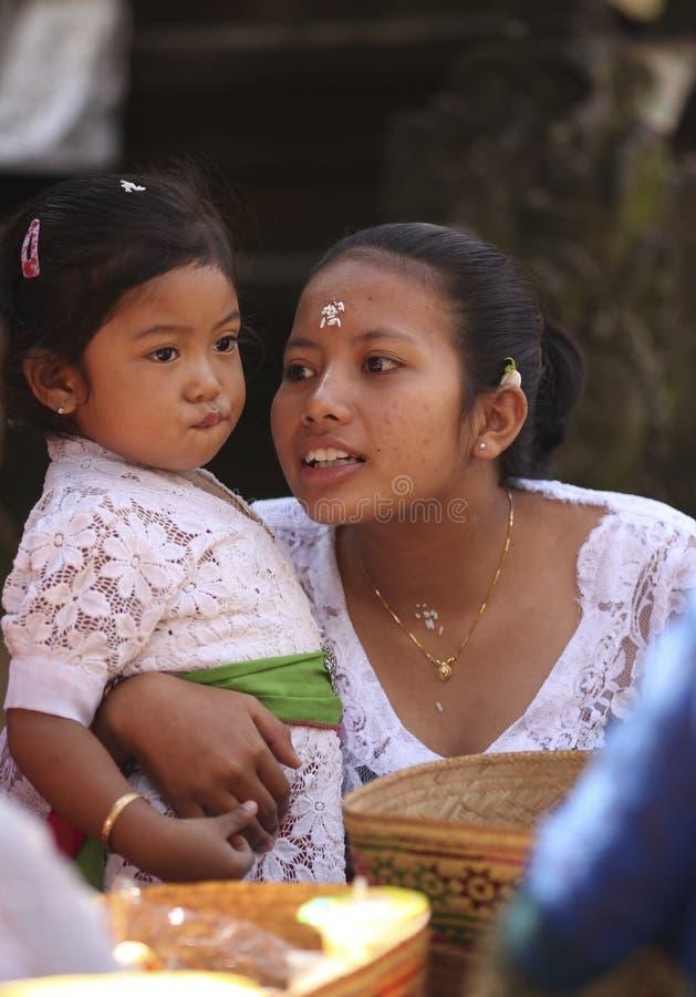 一名巴厘语妇女和她的小孩子传统衣裳的在印度寺庙仪式,巴厘岛,印度尼西亚 免版税库存图片