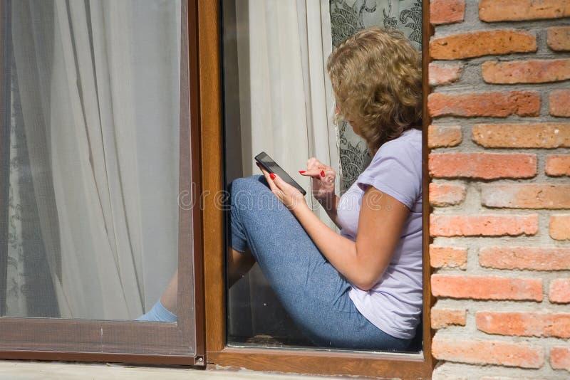 一名年轻俏丽的妇女坐窗台并且举行a 免版税库存照片
