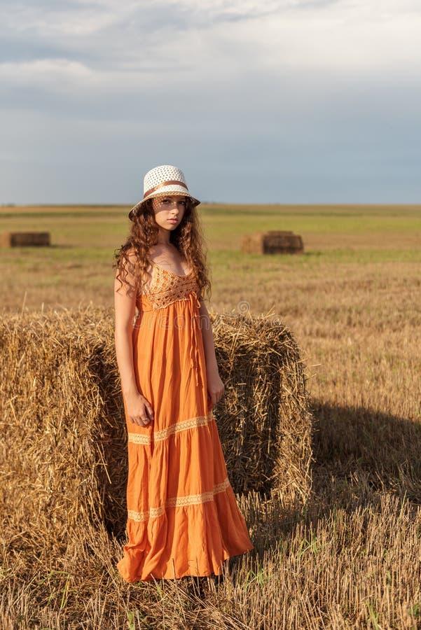 一名年轻农村妇女的画象在一块麦田的一个干草堆附近站立与风雨如磐的天空的sarafan和帽子的 免版税库存照片