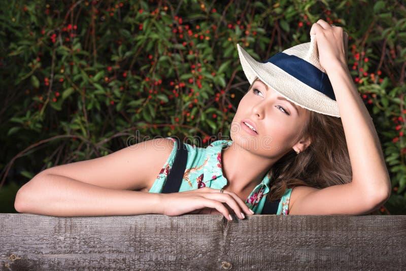 一名年轻可爱的妇女的水平的画象在木篱芭附近的 库存照片