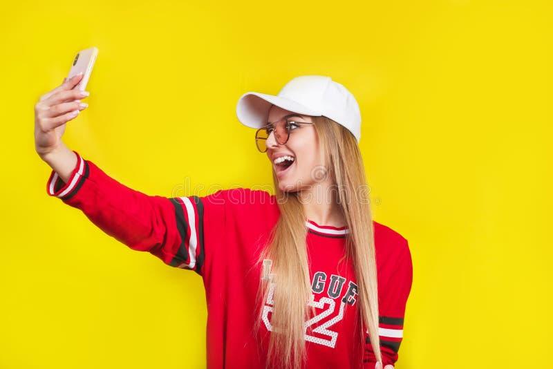 一名年轻可爱的妇女的画象做selfie照片的太阳镜的在黄色背景隔绝的智能手机 图库摄影