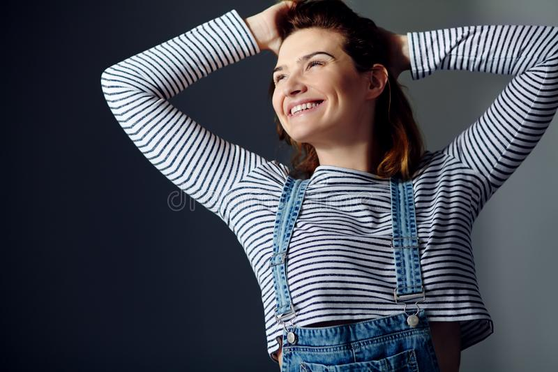 一名年轻可爱的时髦的情感微笑的妇女的画象牛仔裤总体的 免版税库存图片