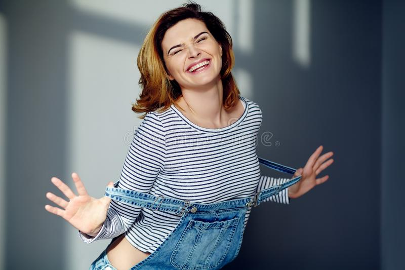 一名年轻可爱的时髦的情感微笑的妇女的画象牛仔裤总体的 图库摄影