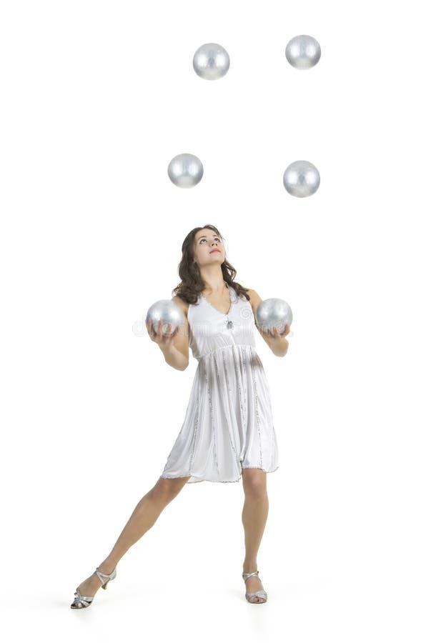 一名年轻女性马戏团演员,玩杂耍银色球 库存图片