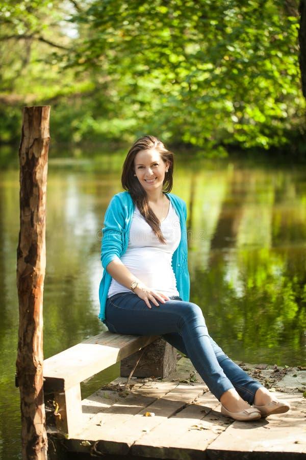 一名年轻孕妇的画象在河附近的 库存照片