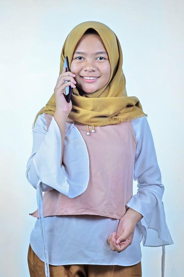 一名年轻学生亚裔妇女的画象谈话在手机,讲话幸福微笑 库存照片