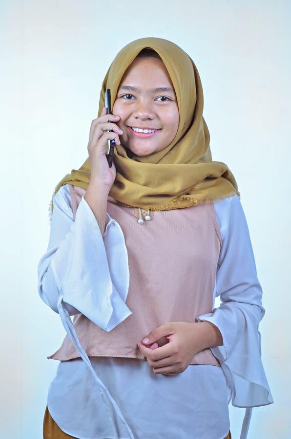 一名年轻学生亚裔妇女的画象谈话在手机,讲话幸福微笑 库存图片