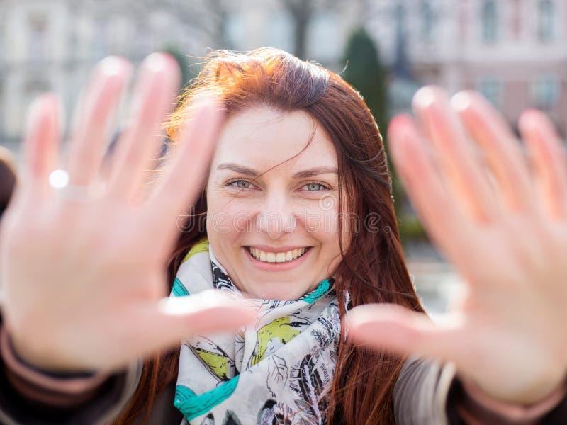 一名年轻微笑的可爱的红头发人妇女的画象在城市背景的春日 妇女显示一个框架从 库存照片