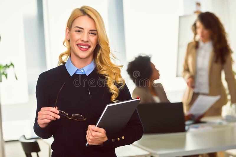 一名年轻微笑的女实业家的画象在不同的妇女的创造性的办公室 库存照片