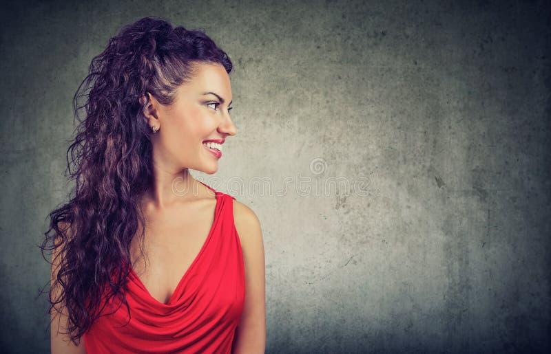 一名年轻微笑的妇女的画象红色礼服的 免版税图库摄影