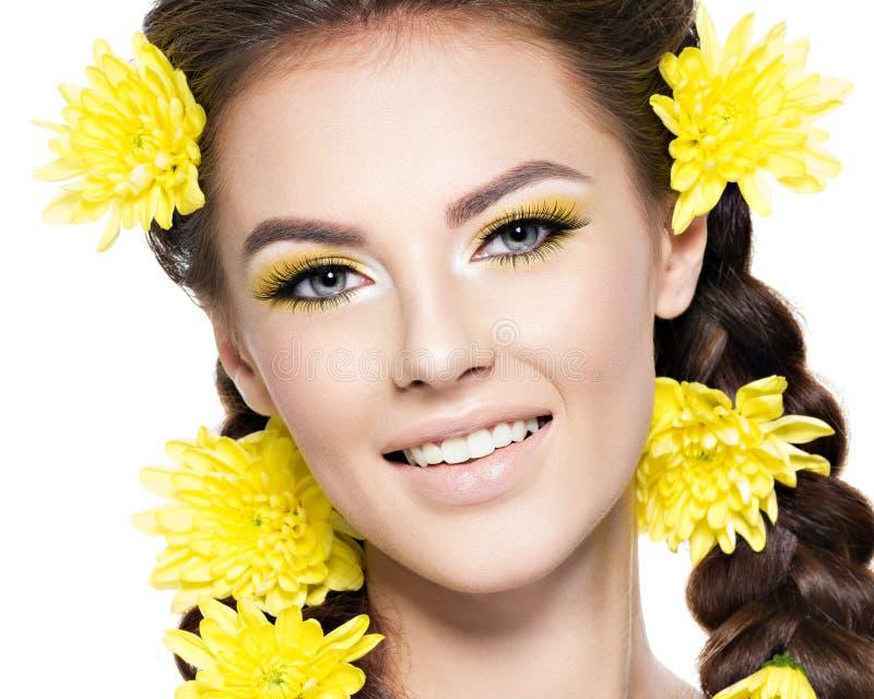 一名年轻微笑的妇女的面孔有明亮的黄色构成的 库存照片