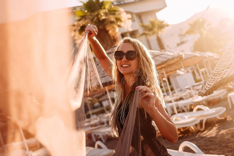 一名年轻微笑的妇女看在塑造外形的日落光的照相机在海滩 库存照片