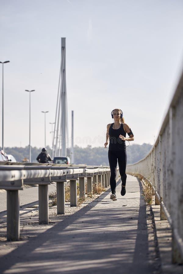 一名年轻微笑的妇女,20-29岁,跑在桥梁 免版税库存照片