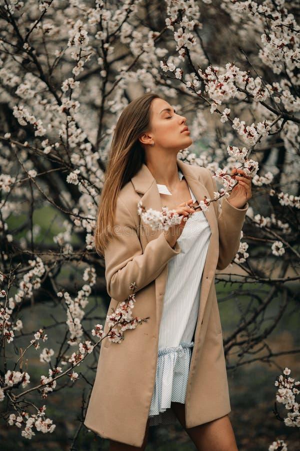 一名年轻愉快的妇女有在开花的庭院中享用 库存图片