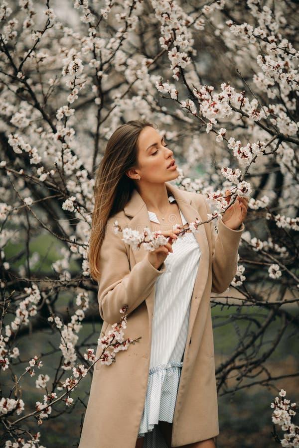 一名年轻愉快的妇女有在开花的庭院中享用 图库摄影