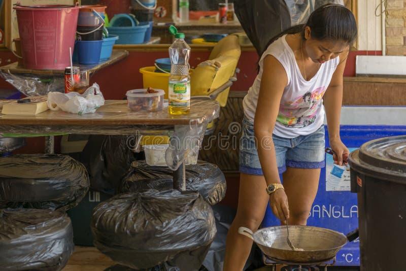 一名年轻泰国妇女烹调在一个小酒吧的食物 免版税库存图片