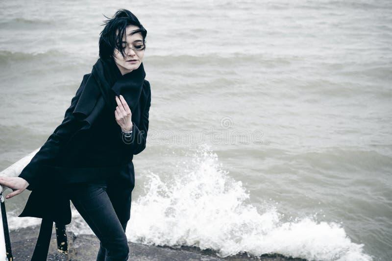 一名年轻深色的妇女的时兴的画象黑衣裳的,牛仔裤T恤杉,外套和太阳镜,在一种哥特式样式哀伤的心情 库存图片