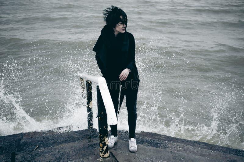 一名年轻深色的妇女的时兴的画象黑衣裳的,牛仔裤T恤杉,外套和太阳镜,在一种哥特式样式哀伤的心情 免版税库存图片