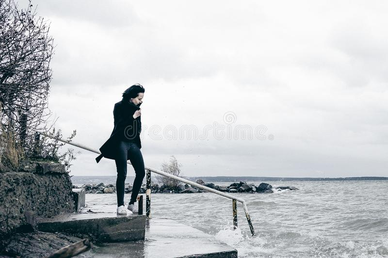 一名年轻深色的妇女的时兴的画象黑衣裳的,牛仔裤T恤杉,外套和太阳镜,在一种哥特式样式哀伤的心情 免版税图库摄影
