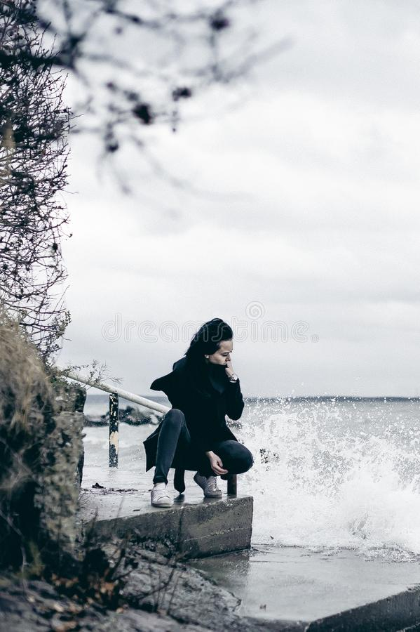 一名年轻深色的妇女的时兴的画象黑衣裳的,牛仔裤T恤杉,外套和太阳镜,在一种哥特式样式哀伤的心情 免版税库存照片
