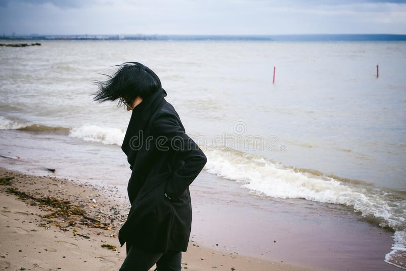 一名年轻深色的妇女的时兴的画象黑衣裳的,牛仔裤T恤杉,外套和太阳镜,在一种哥特式样式哀伤的心情 库存照片