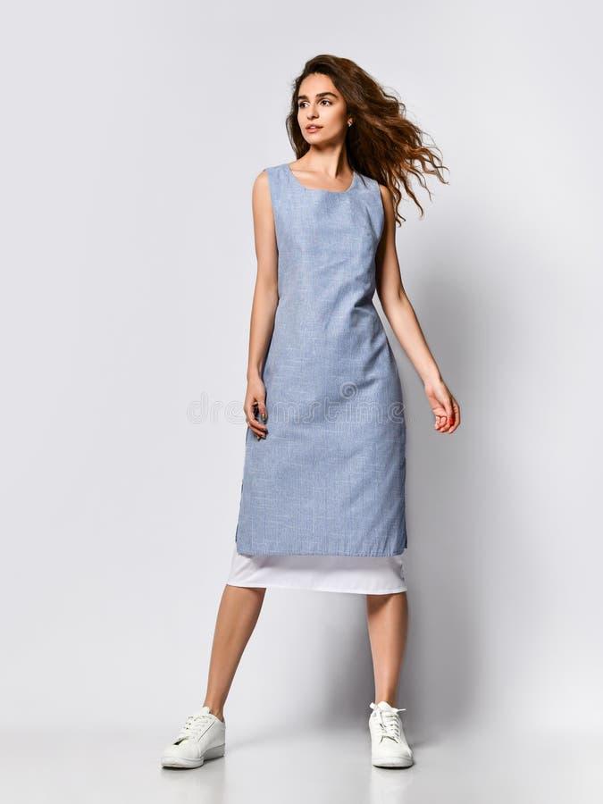 一名年轻深色的妇女的画象摆在轻的背景的一件蓝色轻的礼服的,夏天时尚,为日期做准备 库存照片