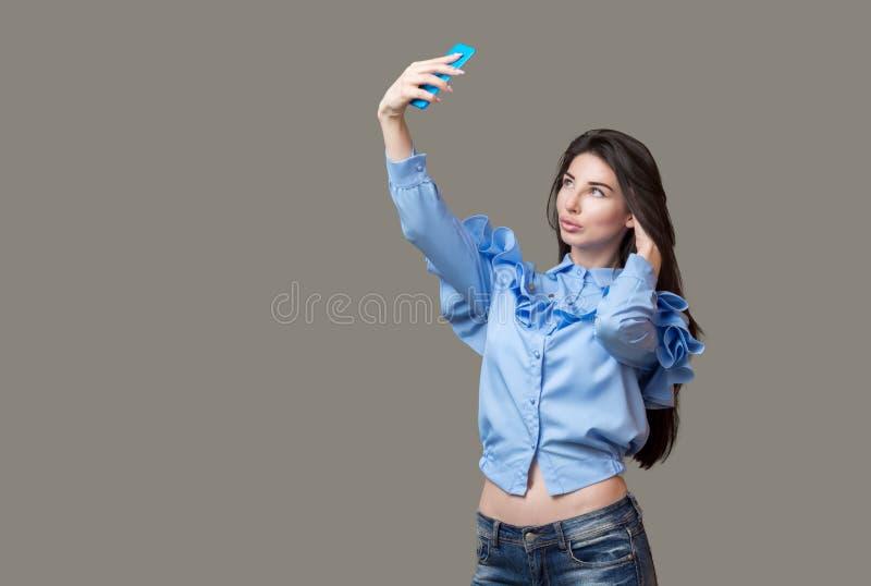 一名年轻深色的妇女的画象蓝色做与她的蓝色电话的衬衣和牛仔裤的一selfie,被隔绝在灰色背景 免版税库存图片