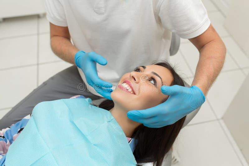 一名年轻男性牙医和愉快的女性患者 牙医办公室生活方式场面 医生实践 耐心医疗保健 库存照片