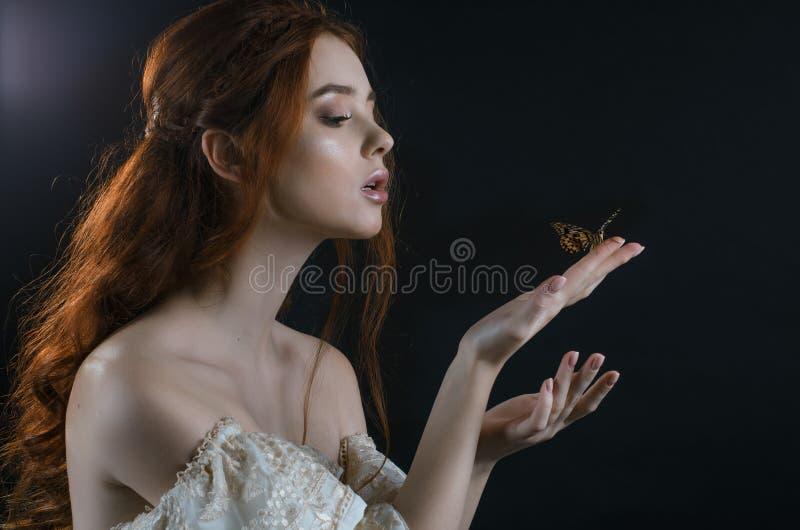 一名年轻红发在月光的妇女有的开背部和肩膀的画象葡萄酒灰礼服的在黑背景 S 库存图片