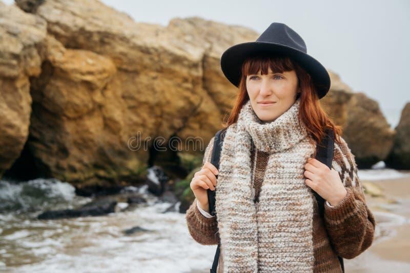 一名年轻红发妇女的画象一个帽子和一条围巾的有以岩石为背景的一个背包的反对 免版税库存照片