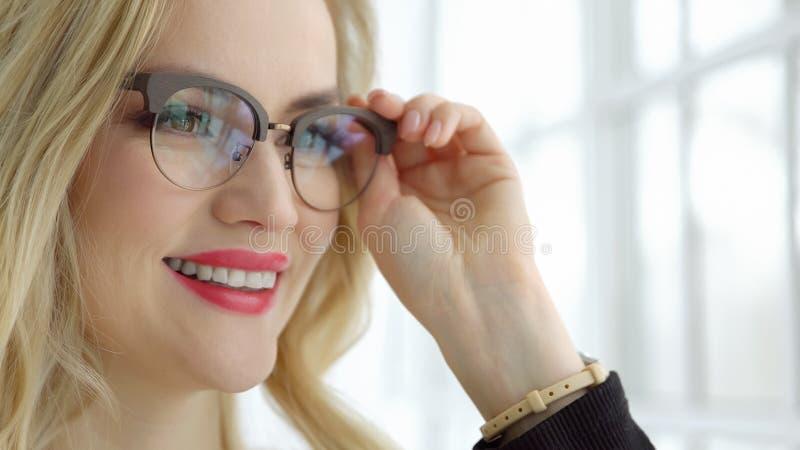 一名年轻美丽的妇女的特写镜头戴眼镜的在窗口 免版税库存照片