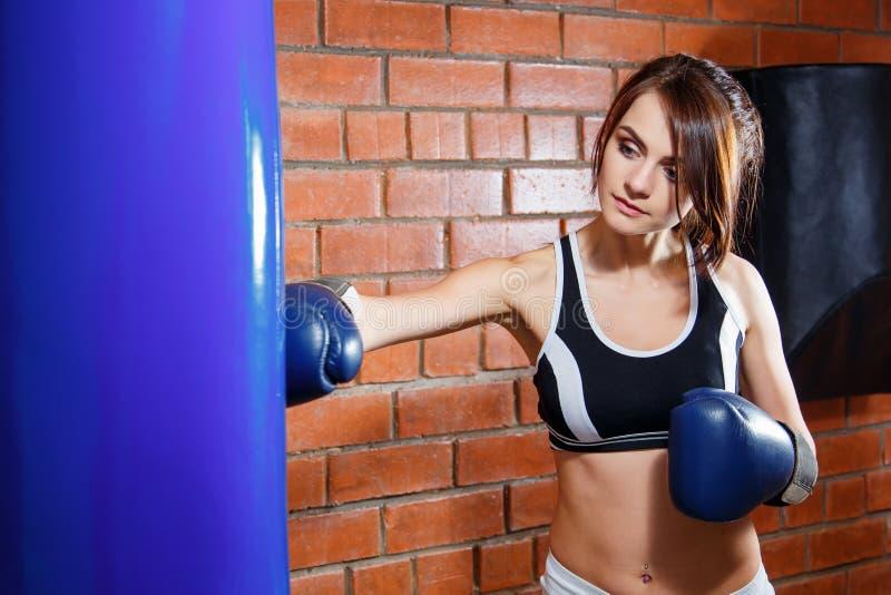 一名年轻美丽的妇女的画象有拳击手套的在健身房的训练 免版税图库摄影