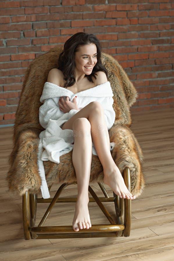 一名年轻美丽的妇女,一件白色特里晨衣的,坐一把摇椅,并且看窗口 背景 图库摄影