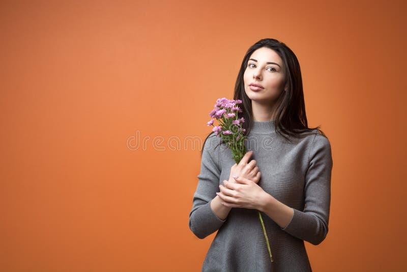 一名年轻美丽的深色的妇女的画象拿着紫罗兰色花和看在照相机的灰色礼服的在她的手上 免版税库存图片