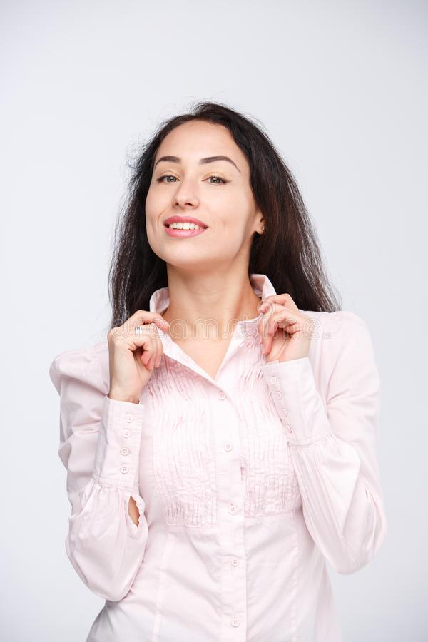 一名年轻美丽的白种人妇女的画象有长的黑发的在一件桃红色衬衣握在一个衣领的手在一轻的backgro 免版税图库摄影