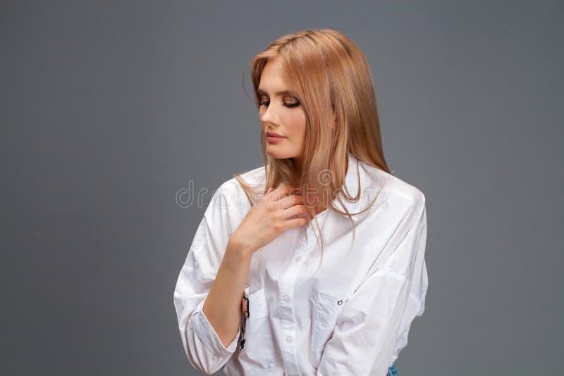 一名年轻美丽的白肤金发的妇女的特写镜头画象白色衬衫的 免版税库存图片