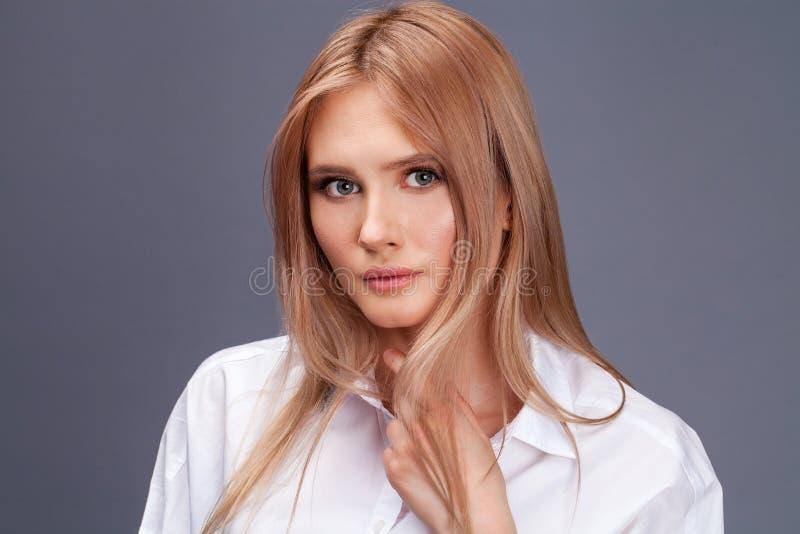 一名年轻美丽的白肤金发的妇女的特写镜头画象白色衬衫的 库存照片