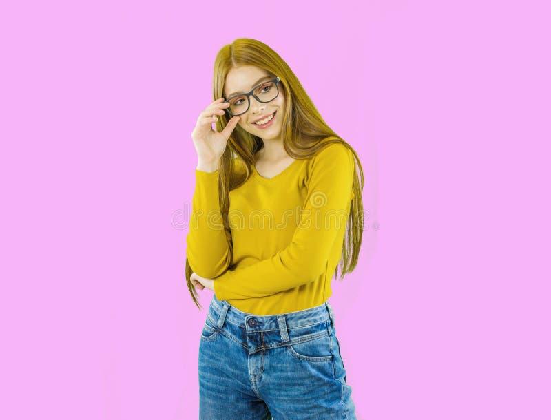 一名年轻美丽的红发妇女的画象微笑的玻璃的看与被降下的玻璃的照相机和,想法 免版税库存照片