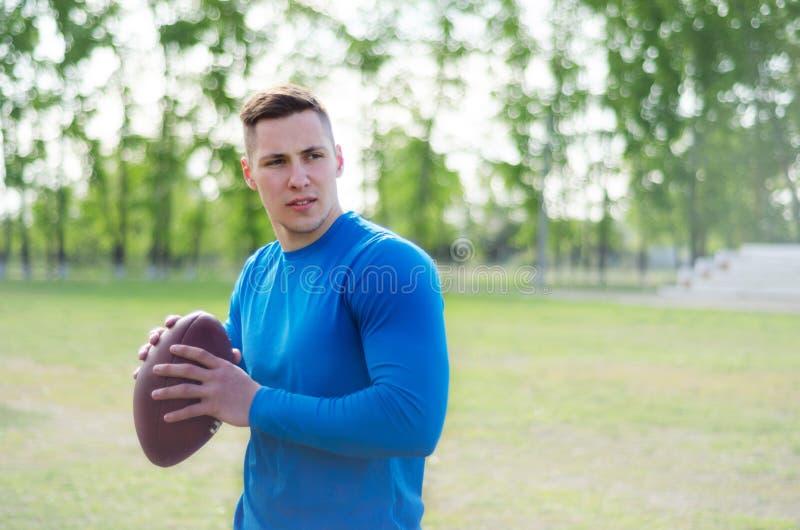 一名年轻美式足球球员的画象有一个球的在训练 免版税库存照片
