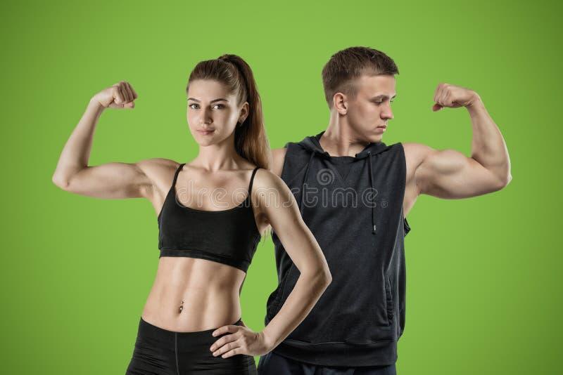 一名年轻肌肉妇女和一个适合的人立场在绿色背景和展示他们强的二头肌 免版税库存照片
