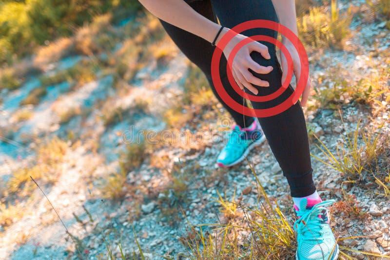 一名年轻运动妇女体验在她的腿的痛苦由于伤害,当跑步在粗糙的地面时 体育的概念和 库存照片