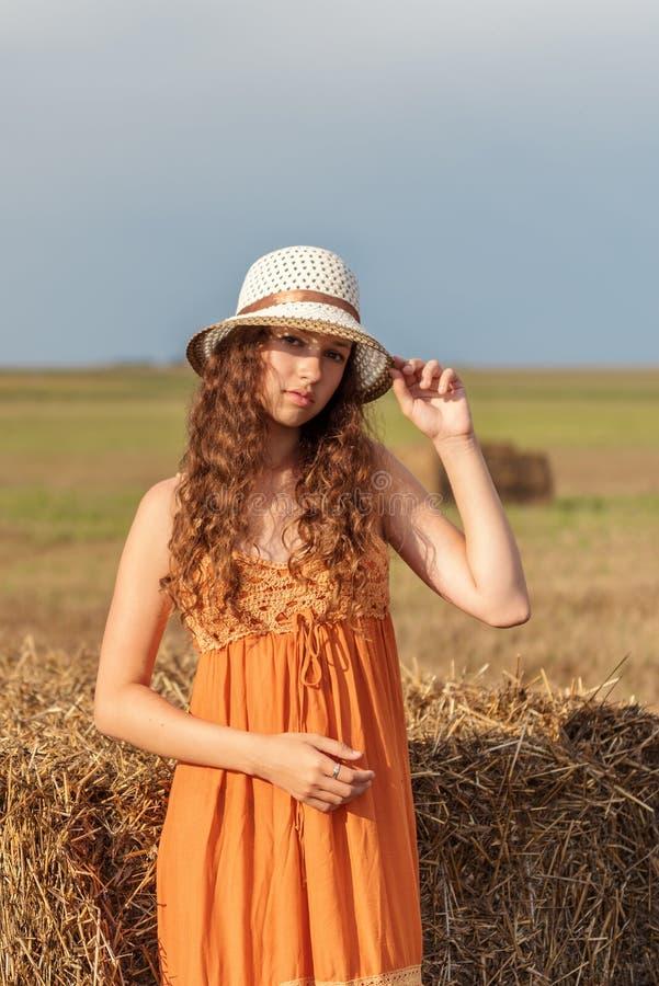 一名年轻逗人喜爱的农村妇女和在堆的一个帽子的垂直的画象橙色sarafan的在一个领域的麦子干草附近在t光芒  库存照片