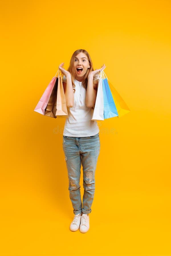 一名年轻震惊妇女的全长画象,愉快在购物与多彩多姿的袋子以后,在黄色背景 免版税库存图片