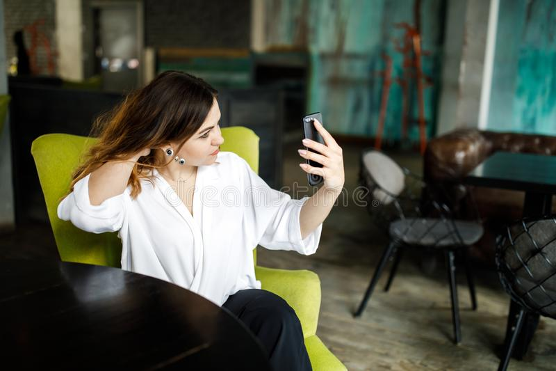 一名年轻,有同情心的妇女,不是一稀薄带头的健美,在一个舒适咖啡馆在她的手上坐,拿着一个智能手机并且整理 免版税库存图片
