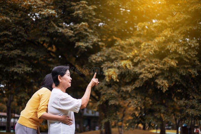 一名年长亚裔妇女的画象有年轻女性的一起指向某事室外早晨,正面认为 库存照片